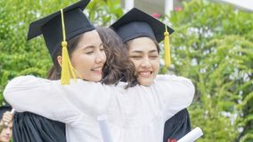 Two asian girl students with the graduation gowns and hat hug th. The two asian girl students with the graduation gowns and hat hug the parent in congratulation Stock Image