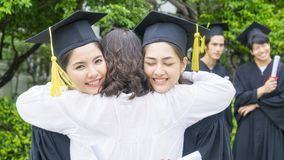 Two asian girl students with the graduation gowns and hat hug th. E parent in congratulation ceremony Royalty Free Stock Photo