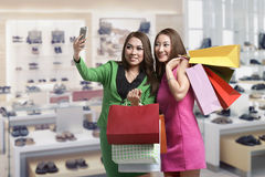 Two asian girl taking selfie with smartphone while holding shopp Royalty Free Stock Photography