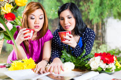 Two Asian girlfriends with fashion magazine Stock Image
