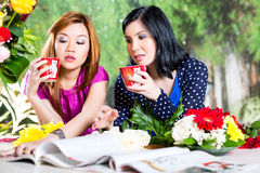 Two Asian girlfriends with fashion magazine Royalty Free Stock Photography