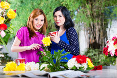 Two Asian girlfriends with flowrers Royalty Free Stock Photography