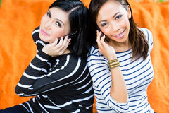Two Asian girlfriends with phone Royalty Free Stock Photography