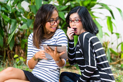 Two Asian girlfriends with tablet computer Royalty Free Stock Photography