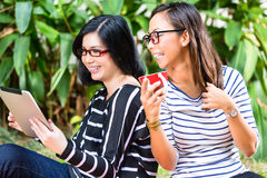 Two Asian girlfriends with tablet computer Stock Photos