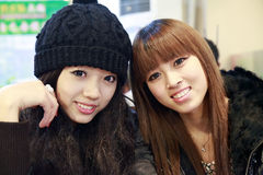 Two Asian girls. Two young asian girls smiling indoors royalty free stock images