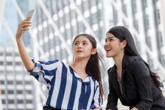 Two asian girls friends taking selfie photo with smartphone in urban. Cute enjoyment 2 accessory background beautiful candid carefree cell cheerful city couple stock image