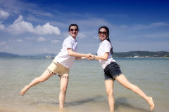 Two asian girls hand in hand on the phuket beach Royalty Free Stock Photography