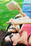 Two asian girls lying on a grass stock images