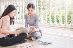 Two asian girls reading book together. Education concept Stock Image