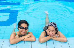 Two Asian girls are relaxing in the swimming pool corner Royalty Free Stock Photography