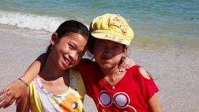 Two Asian girls smiling close-up. Vietnamese girls on the beach closeup are embraced and smiling stock video