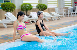 Two Asian girls are splashing water on the swimmin Stock Photos
