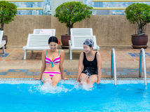 Two Asian girls are splashing water on the swimmin Royalty Free Stock Images