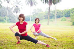 Two Asian girls stretching. Two cheerful Asian girls stretching outdoor green park stock images