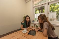 Two asian girls use a tablet while sitting in a cafe and drinking coffee. stock image