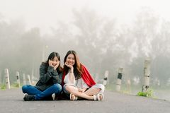 Two asian girls Very close friends Wearing a sweater In tourist attractions Along the road beside the reservoir in the thick fog. With a smiling expression of stock photo