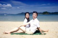 Two asian girsl sitting on the phuket beach Stock Photo