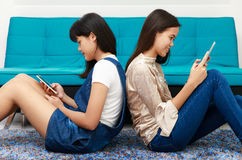 Two Asian grils looking at smatphone and tablet. Two beautiful young teenager Asian girls lay on each back and using mobile devices, smartphone and tablet connet Stock Photography