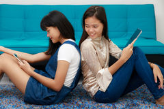 Two Asian grils looking at smatphone and tablet. Two beautiful young teenager Asian girls lay on each back and using mobile devices, smartphone and tablet connet Royalty Free Stock Image