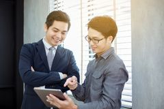 Two Asian handsome businessmen using touchpad with partners disc. Ussing documents and ideas at meeting and smiling happy for working Royalty Free Stock Photos