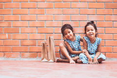 Two asian kid girls sitting on the floor and playing together Stock Images