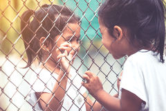 Two asian kids talking to each other and hand holding steel mesh. In vintage color tone royalty free stock photo