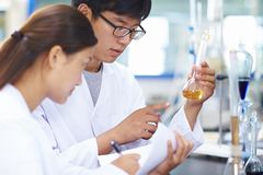Two Asian Laboratory scientist working at lab with test tubes Stock Images