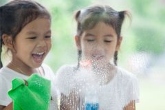 Two asian little child girls help parent to clean window. Two asian little child girls having fun to help parent to clean window together royalty free stock photos