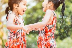 Two asian little child girls holding hand jumping and play water. Two asian little child girls holding hand jumping and playing water together in summer time stock images