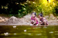 Two asian little child girls playing paper boat in the riverside Royalty Free Stock Photos