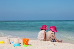 Two asian little child girls sitting and playing with sand together on the beach near the beautiful sea in summer vacation stock image