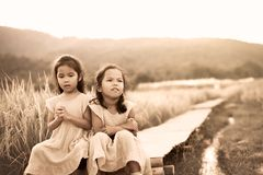Two asian little child girls who feel bored and sad Royalty Free Stock Image