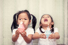 Two asian little girl having fun to blowing birthday cupcake Stock Images