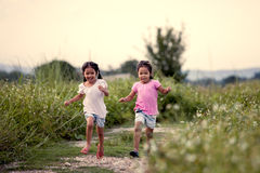 Two asian little girls having fun and running together. In the park in vintage color tone Royalty Free Stock Photo