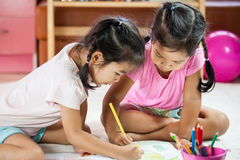 Two asian little girls having fun to paint with crayon. Together in vintage color tone stock photo
