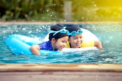 Two asian little girls having fun to swim in swimming pool. Together Stock Photos