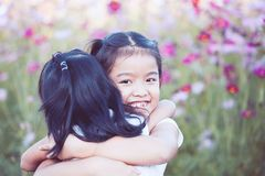 Two asian little girls hugging each other with love. In the cosmos flower field in  vintage color tone Stock Photography