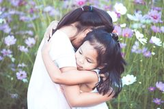 Two asian little girls hugging each other with love. In the cosmos flower field in  vintage color tone Stock Photos