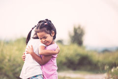 Two asian little girls hugging each other with love. In vintage color tone Royalty Free Stock Image