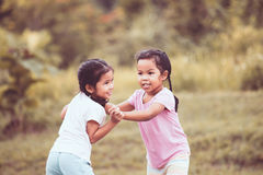 Two asian little girls playing together in the park. In vintage color tone Stock Photo