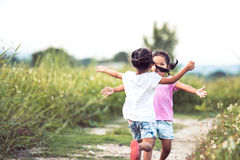 Two asian little girls running to give a hug each other. In vintage color tone stock photography