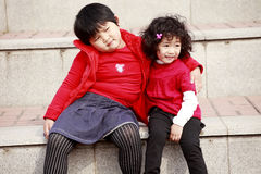 Two Asian little girls on stairs. royalty free stock photos