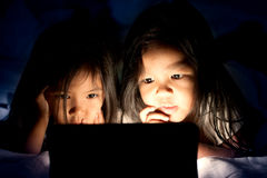Two asian little girls using digital tablet at night. In the bedroom in dark blue color tone stock photo