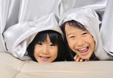 Two asian Little kids peeking out from a curtain Royalty Free Stock Image