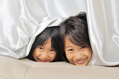 Two asian Little kids peeking out from a curtain Stock Photos