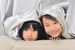 Two asian Little kids peeking out from a curtain Royalty Free Stock Images
