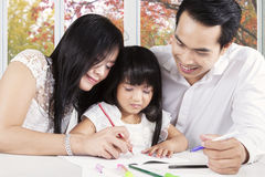 Two asian parents teach their child to write Stock Image