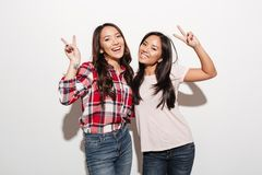 Two asian pretty cheerful ladies sisters showing peace gesture. Image of two asian pretty cheerful ladies sisters hugging with each other. Looking camera stock photography