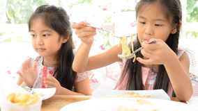 Two Asian pretty girls with fork in hands eats pasta, close-up.  stock footage